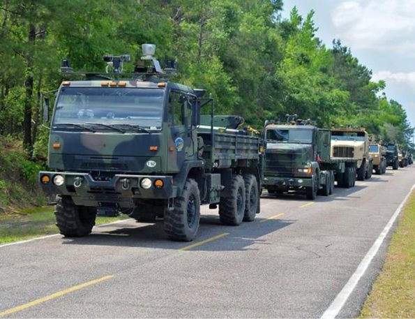 Seven unmanned military trucks photographed during a test of the Army's autonomous mobility system